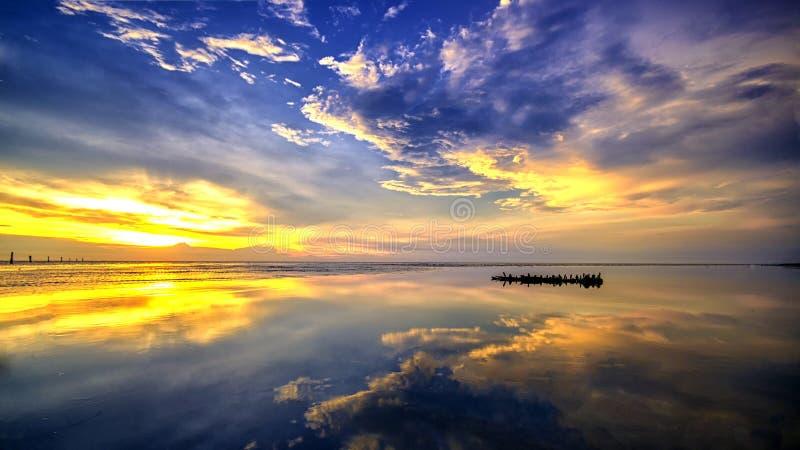 Barca del relitto durante il tramonto alla spiaggia fotografia stock