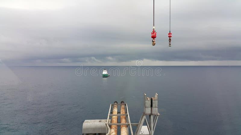 Barca del rifornimento che viene all'impianto offshore immagini stock libere da diritti