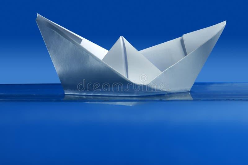 Barca di carta che galleggia sopra l'acqua reale blu fotografia stock libera da diritti