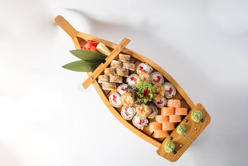 Barca di legno con i lotti dei sushi con lo zenzero ed il wasabi fotografia stock