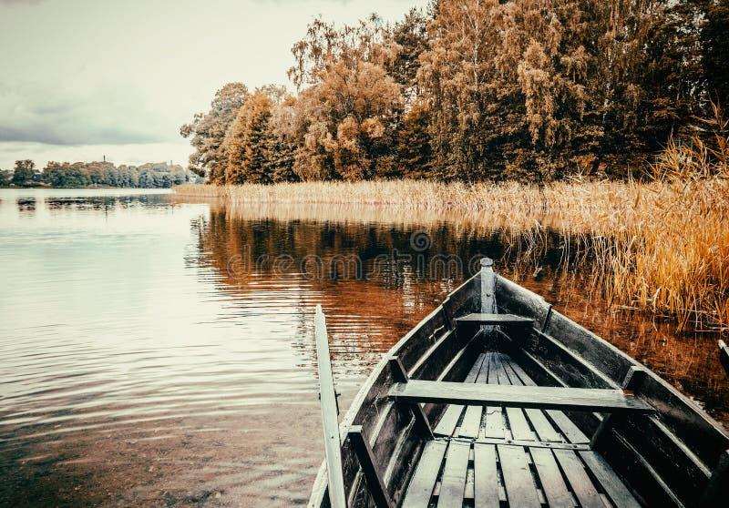 Barca di legno con i remi sulla riva del lago in un autum luminoso immagini stock libere da diritti