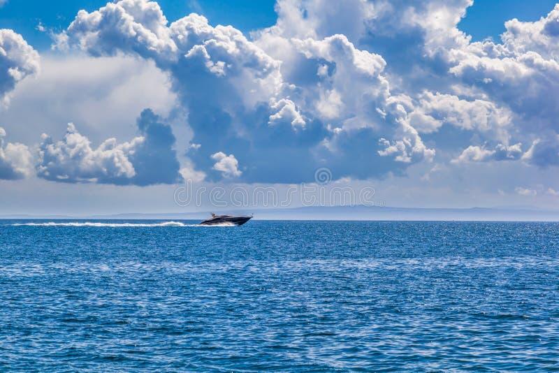 Barca di velocità sul mare blu con il cielo nuvoloso fotografia stock