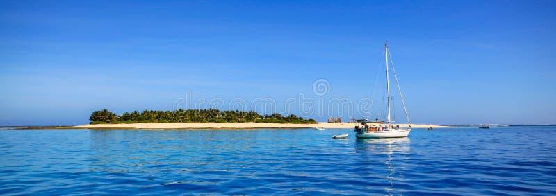Barca e bella isola dell'atollo del Fiji con la spiaggia bianca fotografia stock