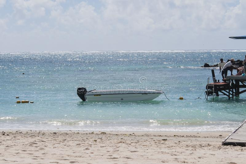 Barca legata alla piattaforma in acqua di luccichio sulla spiaggia sabbiosa, con cielo blu esile nel fondo fotografie stock