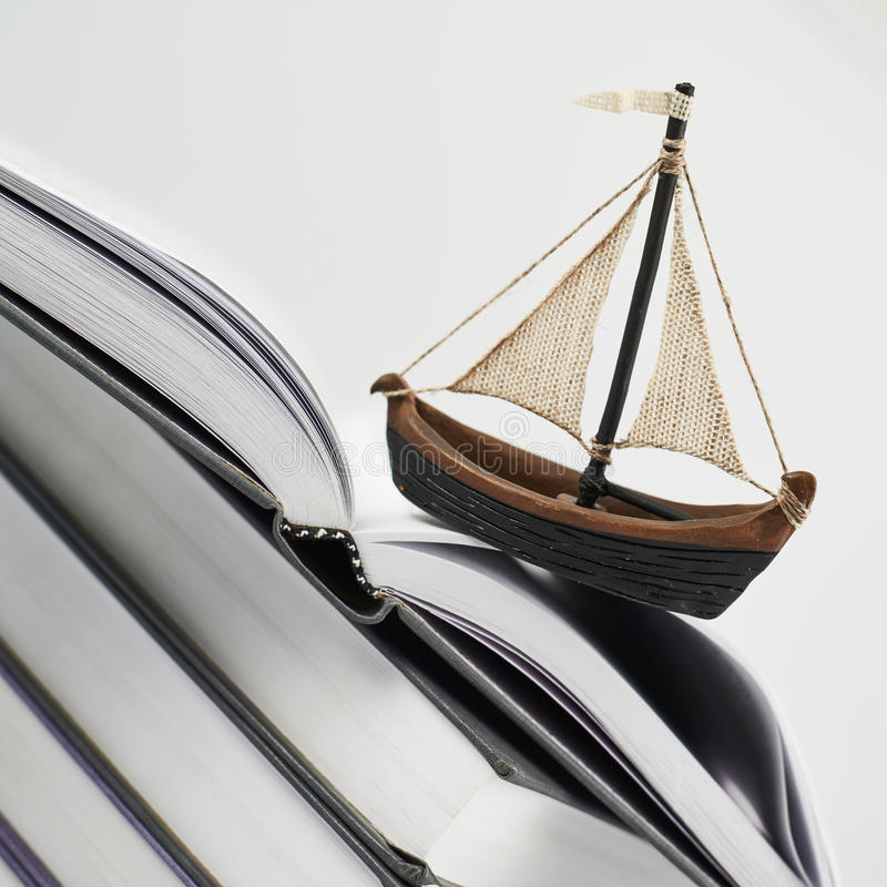 Barca minuscola sopra la pagina di un libro aperto immagini stock