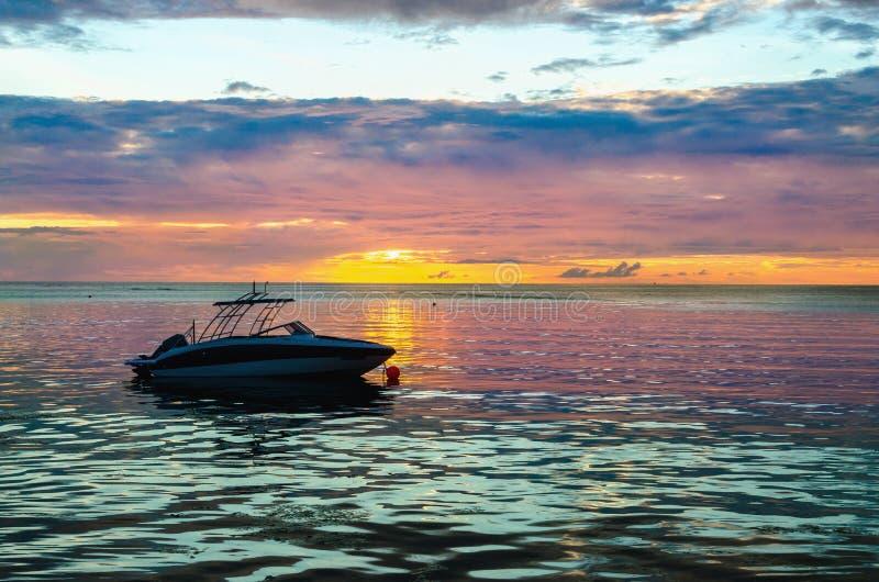 Barca nell'oceano al tramonto immagine stock