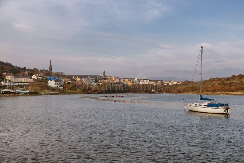 Barca nella baia di Clifden con il villaggio nel fondo fotografia stock
