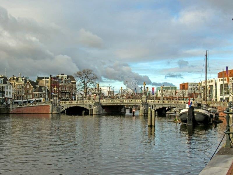 Barca, ponte e costruzioni di mattone fiamminghe tradizionali olandesi famose di Amsterdam a Amsterdam, Olanda, Paesi Bassi immagini stock