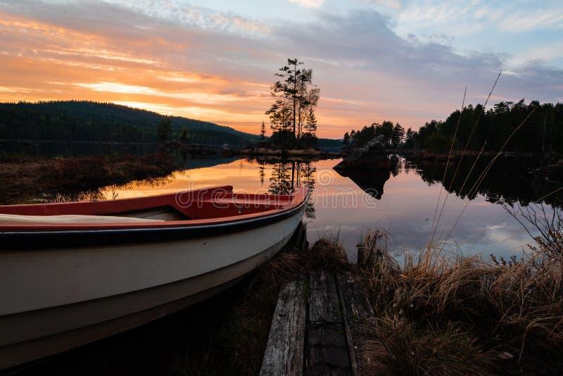 Barca pronta per la pesca in un lago calmo con un tramonto adorabile fotografia stock libera da diritti