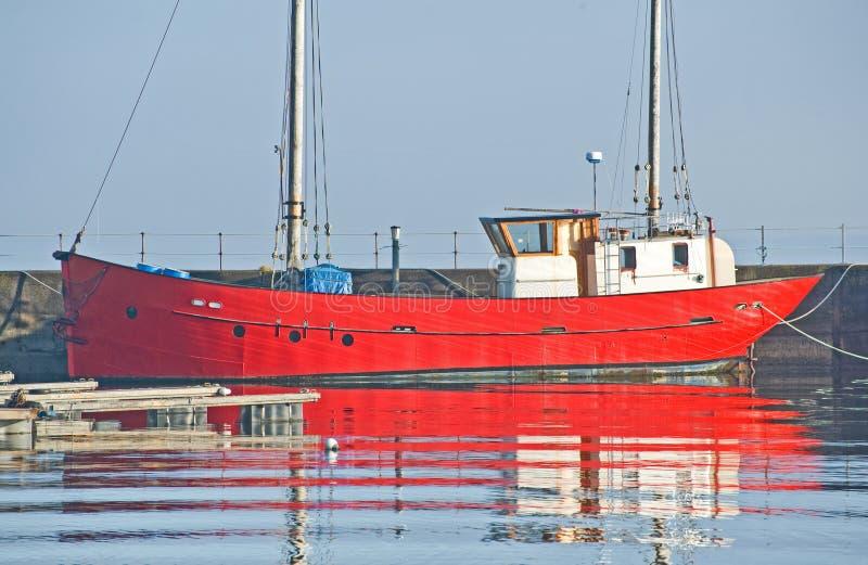 Barca rossa con la timoniera bianca in porto. immagine stock libera da diritti