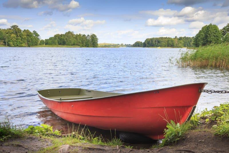 Barca rossa sulla riva su fondo di paesaggio pittoresco del lago e della natura verde intorno nel giorno di estate soleggiato lum immagini stock libere da diritti