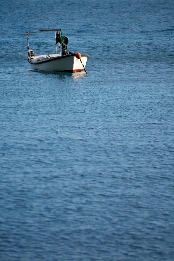 Barca sola del pescatore sul mare blu fotografia stock libera da diritti