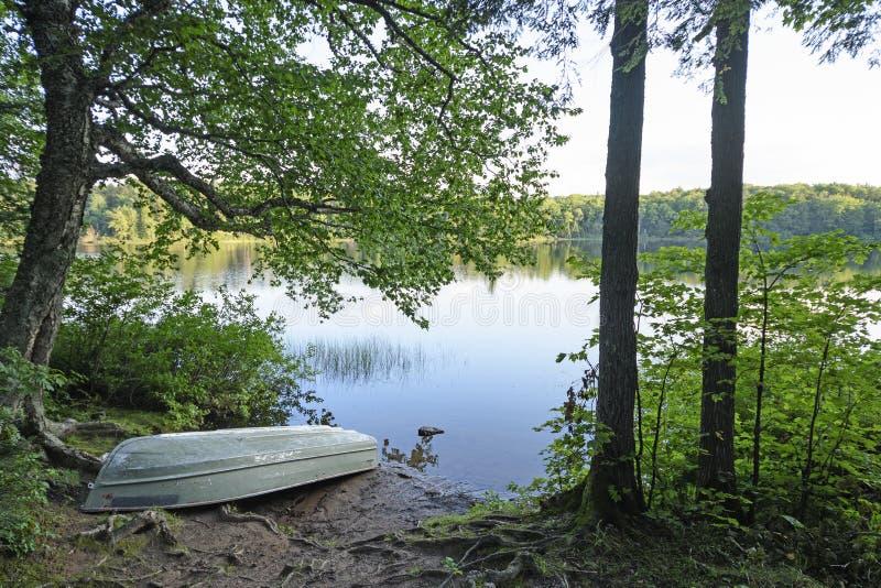 Barca sulla riva di un lago calmo fotografia stock libera da diritti