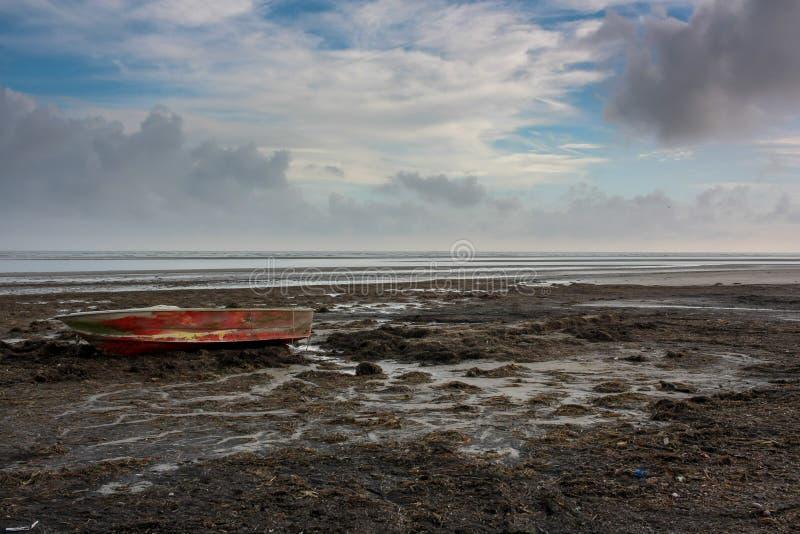 Barca sulla spiaggia dopo una tempesta fotografia stock