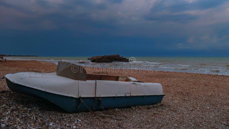 Barca sulla spiaggia prima della tempesta Nubi drammatiche immagini stock