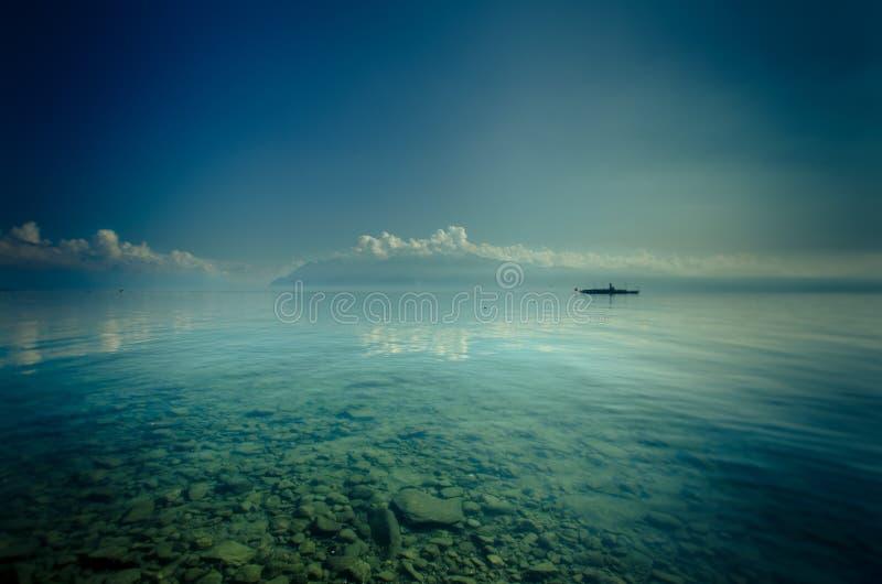 Barca sulle acque trasparenti del lago fotografie stock