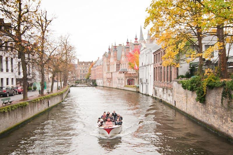 Barca turistica lungo il canale nel paesaggio medievale del Belgio, di Bruges con i vecchi ponti e le costruzioni storiche fotografia stock