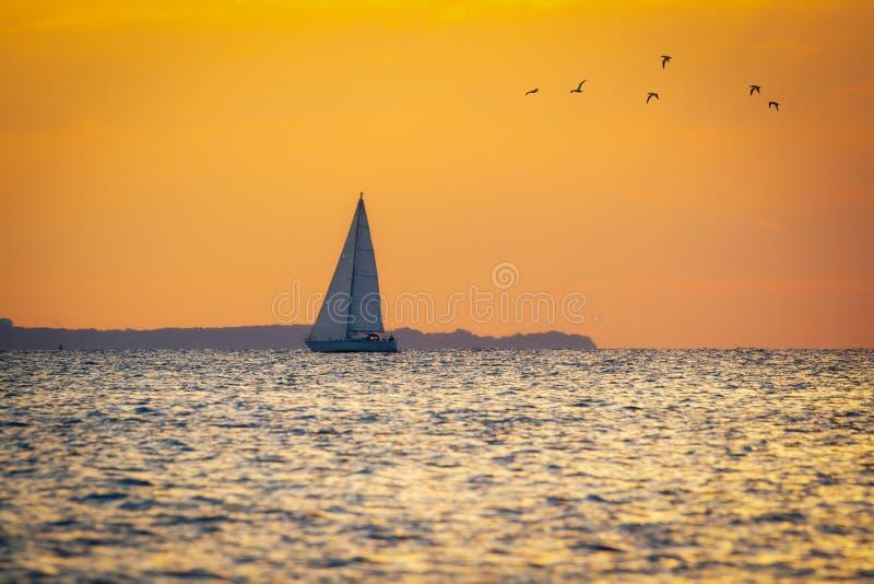 Barca a vela al tramonto nella baia immagine stock libera da diritti