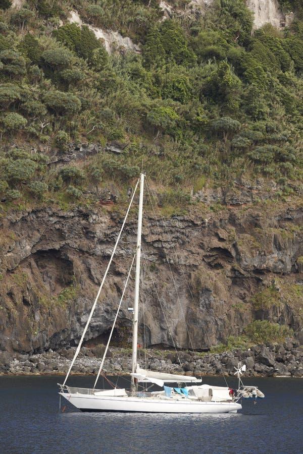 Barca a vela ancorata in entrata del porto dell'isola del Flores Le Azzorre, Portug fotografia stock