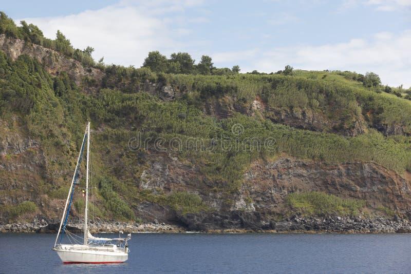 Barca a vela ancorata in entrata del porto dell'isola del Flores Le Azzorre, Portug immagine stock