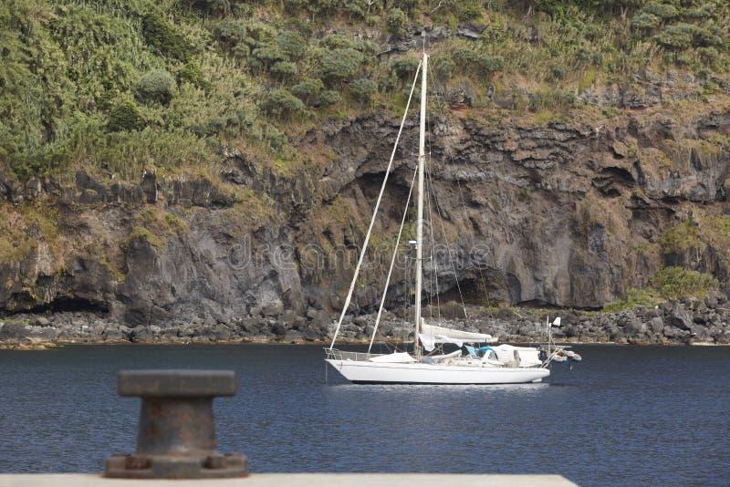 Barca a vela ancorata in entrata del porto dell'isola del Flores Le Azzorre, Portug fotografie stock libere da diritti