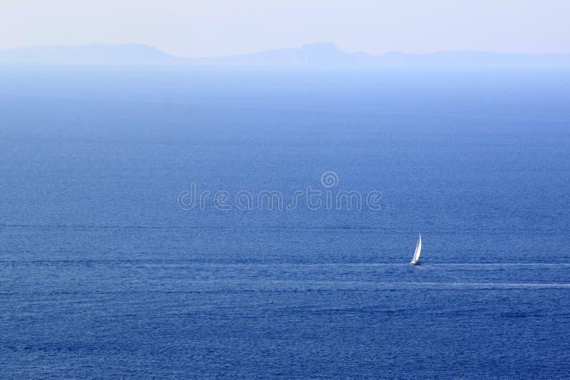 Barca a vela bianca sola nello spazio del mare fra le onde del blu e l'orizzonte lontano fotografia stock