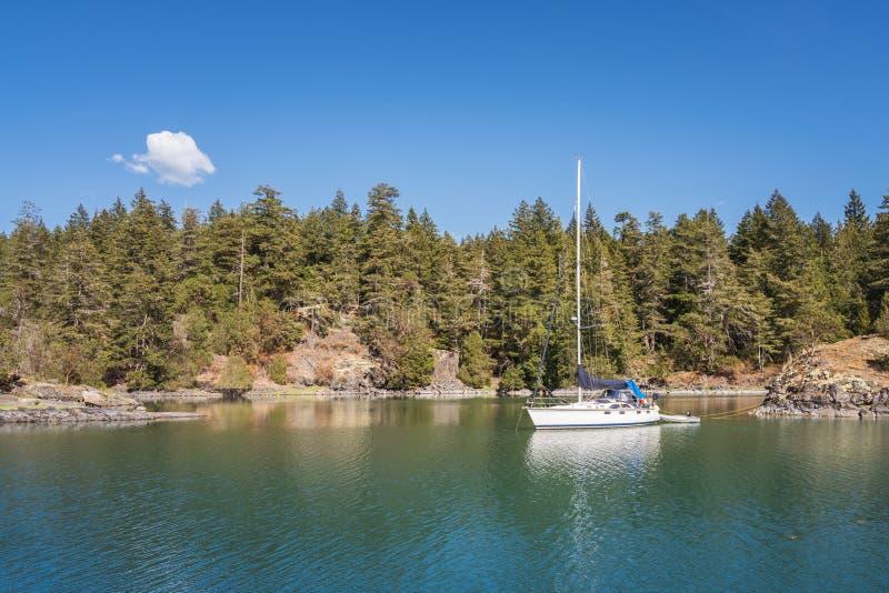 Barca a vela con gli ambiti di provenienza del cielo blu alla baia Marine Provincial Park del contrabbandiere immagine stock libera da diritti