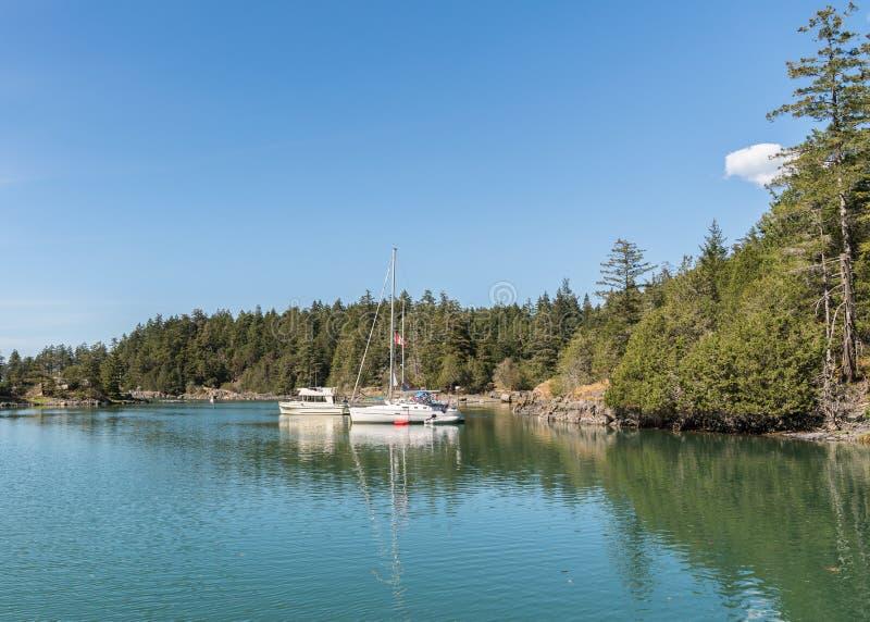Barca a vela con gli ambiti di provenienza del cielo blu alla baia Marine Provincial Park del contrabbandiere fotografia stock libera da diritti