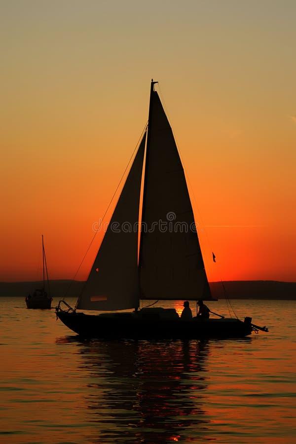 Barca a vela con la gente nel tramonto immagini stock libere da diritti