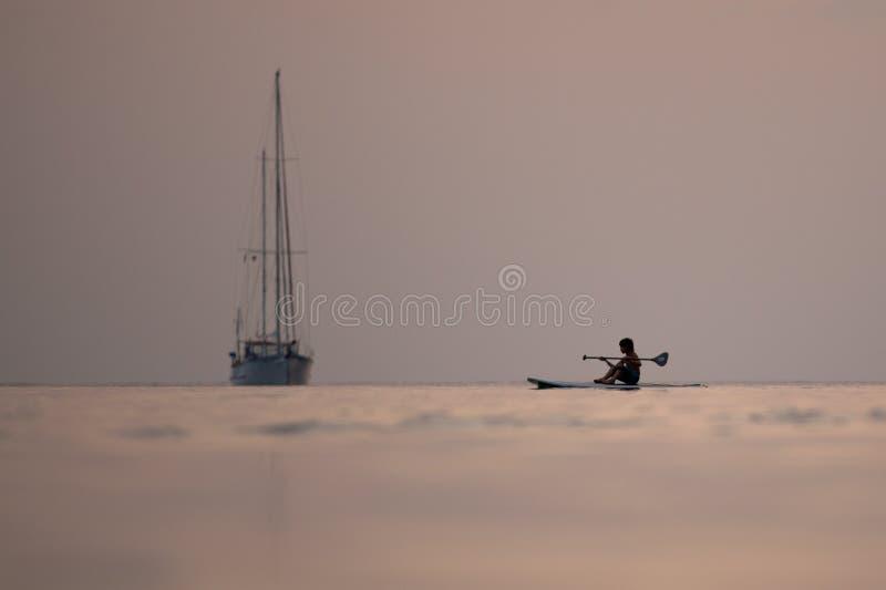 Barca a vela di tramonto e giovane surfista fotografia stock