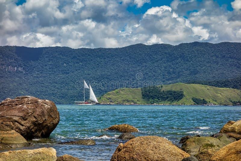 Barca a vela in mare le rocce viste attraverso sulla spiaggia il giorno soleggiato con il cielo nuvoloso a Ilhabela - Sao Paulo,  fotografie stock libere da diritti