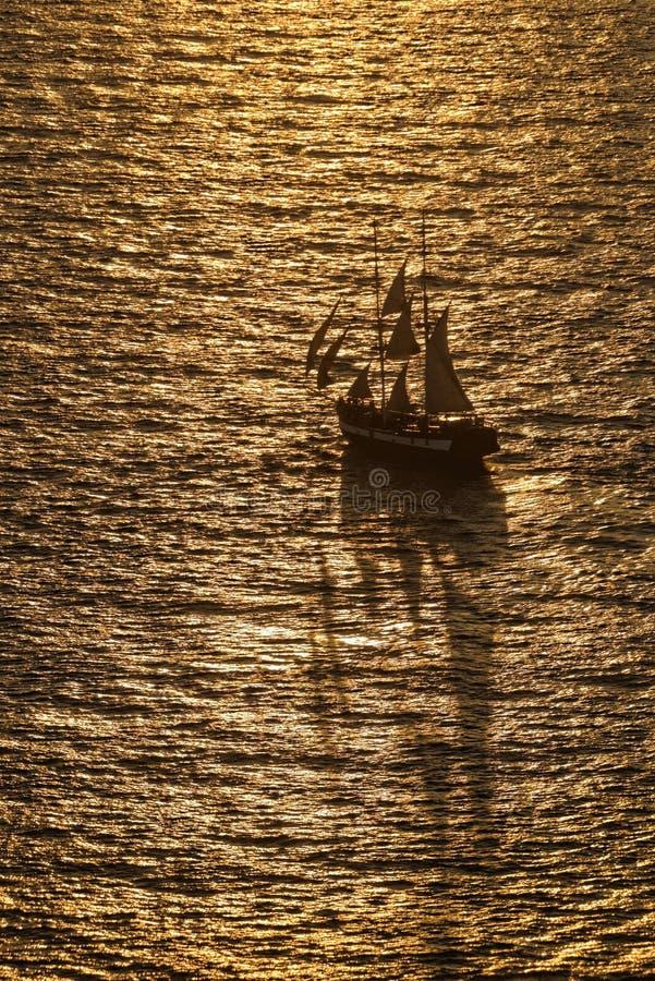 Barca a vela in oceano dorato immagine stock