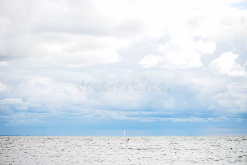 Barca a vela sola in mare, cielo nuvoloso ed acqua dell'argento immagini stock