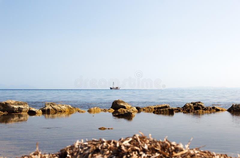 Barca a vela sola nel mare sull'orizzonte immagine stock