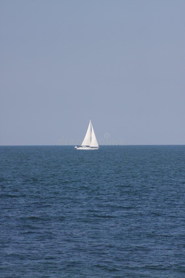 Barca a vela sola sul mare fotografia stock