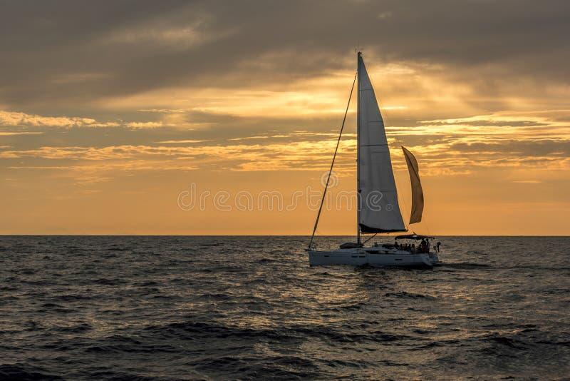 Barca a vela sul mare aperto durante il tramonto sotto i cieli nuvolosi immagini stock