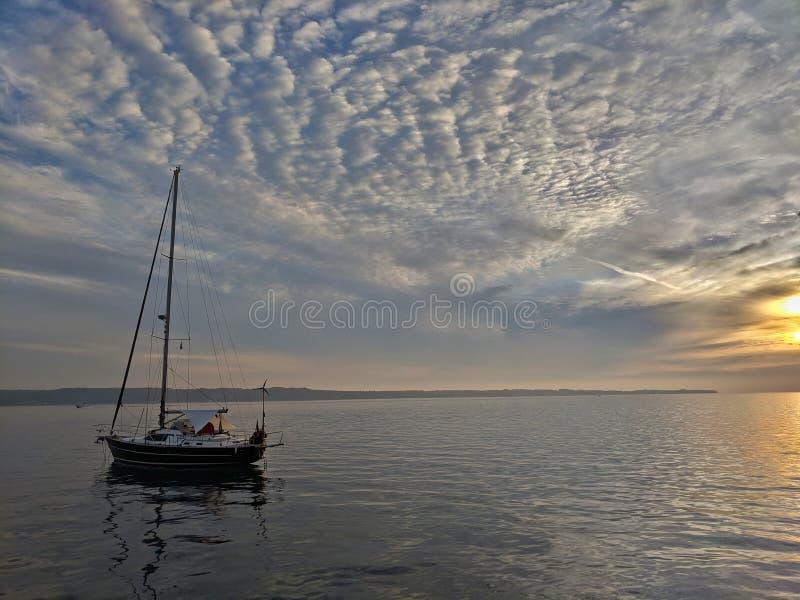Barca a vela sul mare nel tramonto con il cielo nuvoloso strutturato fotografia stock libera da diritti