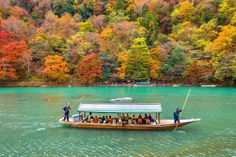 Barcaiolo che calcia la barca al fiume Arashiyama nella stagione di autunno lungo il fiume a Kyoto, Giappone fotografia stock libera da diritti