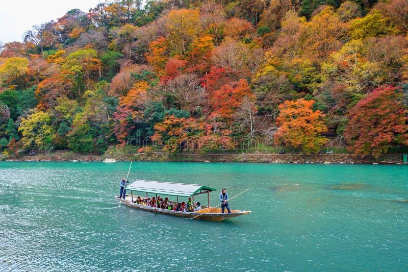 Barcaiolo che calcia la barca al fiume Arashiyama nella stagione di autunno lungo il fiume a Kyoto, Giappone fotografia stock