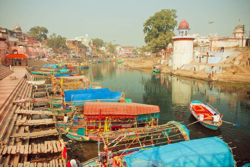 Barcas coloridas que flotan en el río reservado del agua de la ciudad india con las casas históricas imagenes de archivo