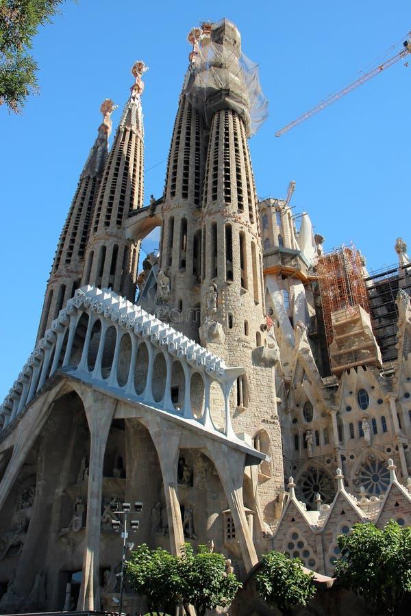 Barcellona, Spagna, agosto 2016 Vista della facciata della cattedrale della famiglia e delle gru di costruzione sante contro il c immagini stock