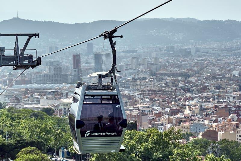 Barcellona, Spagna - maggio, 27 2018: Cabina della cabina di funivia con Barcellona storica su fondo fotografia stock libera da diritti