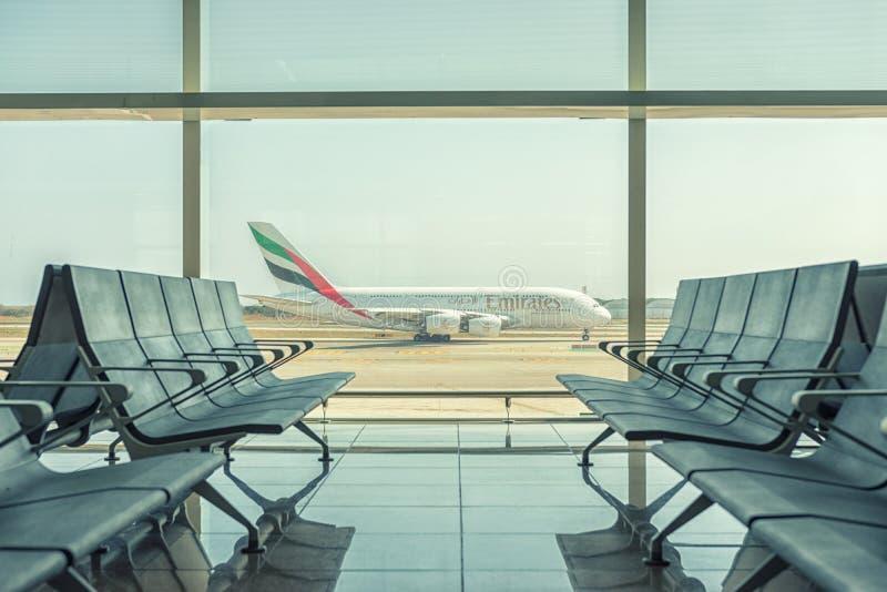 Barcelona, †‹â€ ‹Spanje - 17 Maart, 2019: Lege stoelen in de vertrekzaal bij luchthaven op achtergrond van vliegtuig het opstij stock foto