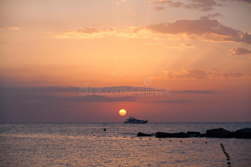 Barcelona sunrise with yacht on sea stock images