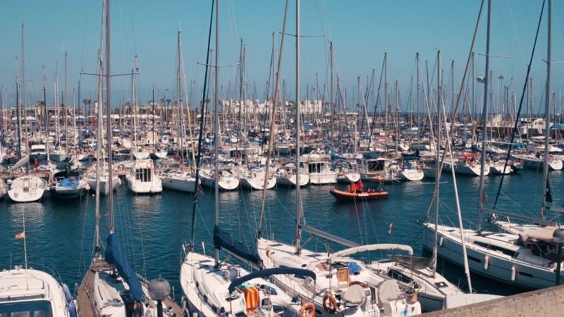 BARCELONA, ESPAÑA - ABRIL, 15, 2017 Steadicam tiró de veleros amarrados en los embarcaderos del puerto deportivo foto de archivo