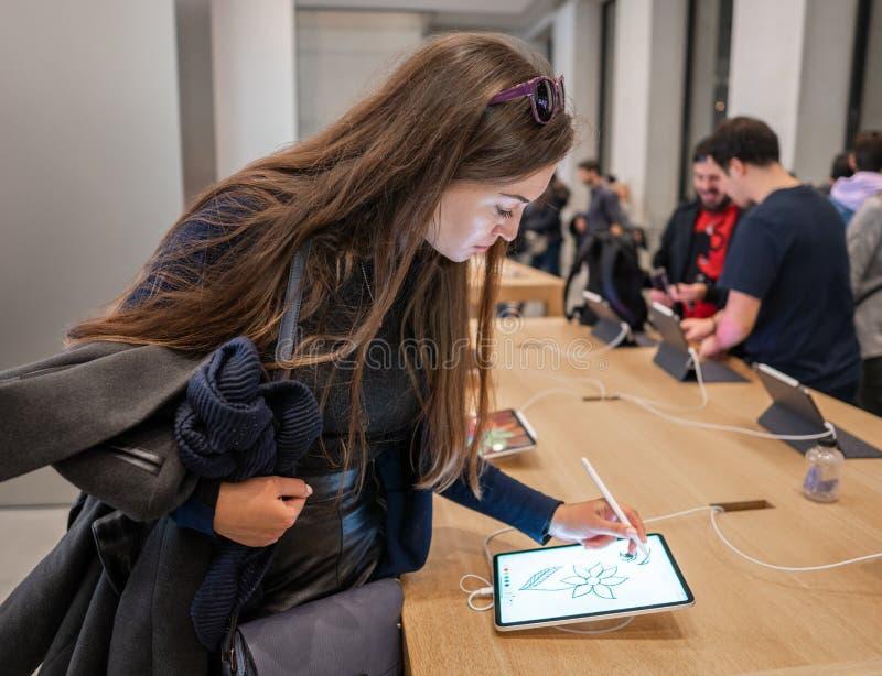 Barcelona, España - 7 de noviembre de 2018: Mujer que lleva a cabo un nuevo iPad favorable fotos de archivo