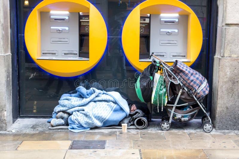 BARCELONA, ESPAÑA, el 4 de febrero de 2018 hombre sin hogar cubierto con bla fotos de archivo