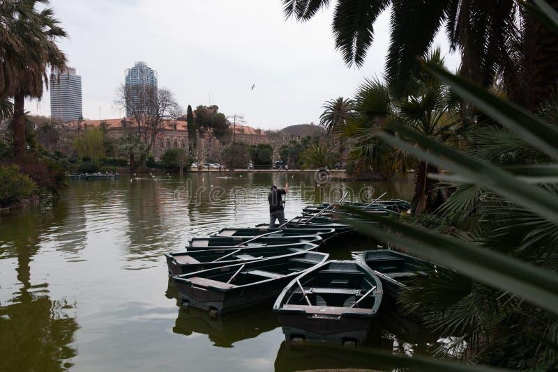 Barcelona, España, marzo de 2016: el trabajador examina los barcos de placer en la charca del parque de la ciudad foto de archivo