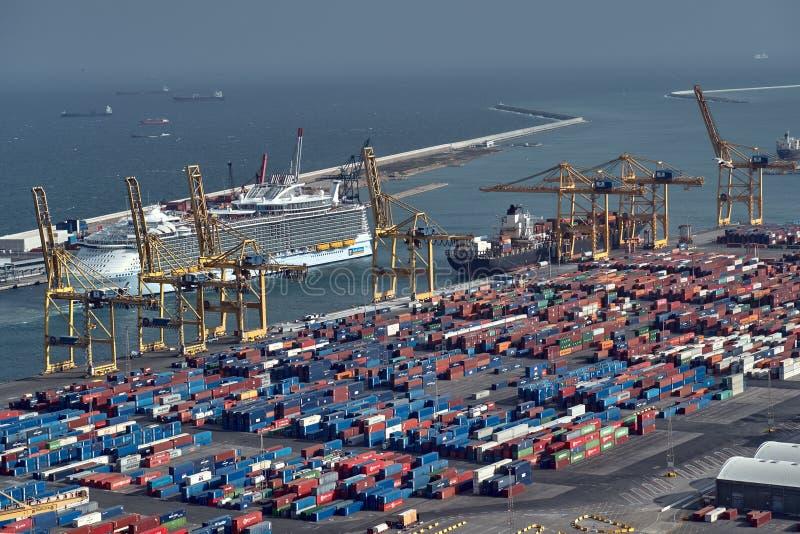 Barcelona, España - mayo, 27 2018: Contenedores para mercancías del metal azul y rojo que son cargados en buque de carga por la g fotografía de archivo libre de regalías