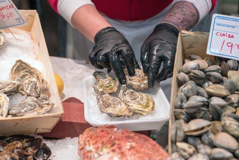 BARCELONA, ESPANHA - 13 de março de 2019: Um homem está abrindo uma ostra fresca no mercado de peixes imagem de stock royalty free